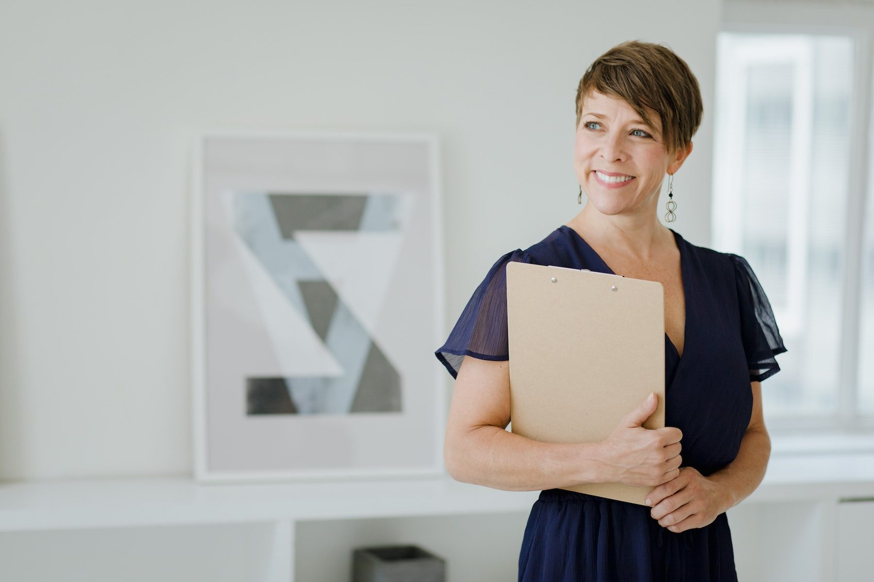 Smiling EFT Practitioner holding a clipboard in her office